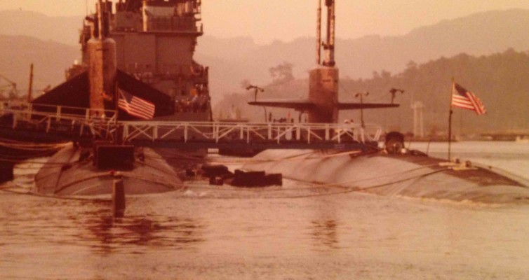 Behind a guided missile destroyer, A 637 Class Fast Attack (notice the vertically positioned sail planes) tied inboard of USS Bremerton in a WestPac port, probably Subic Bay, Philippines, circa 1983.